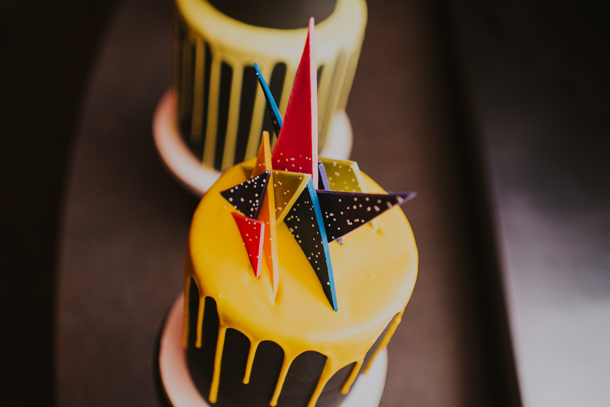 black petite fours with yellow drip and geo shapes