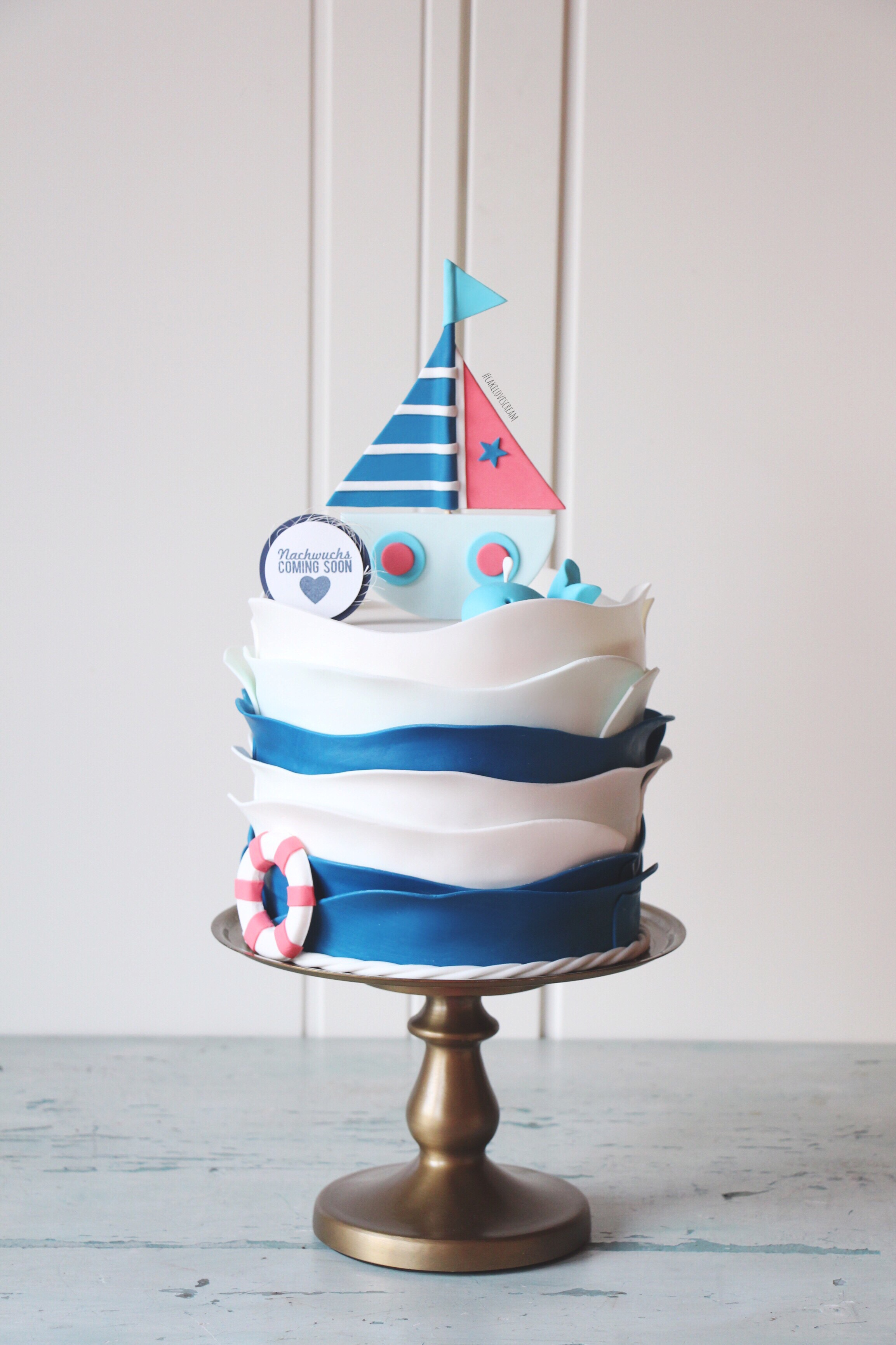 Blue and white ruffle nautical cake with boat topper