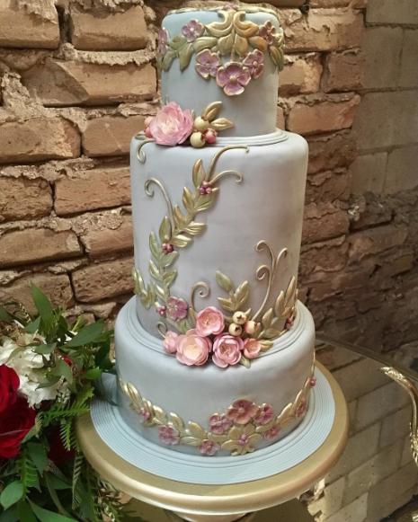 Light blue wedding cake with orange gold decor and sugar flowers