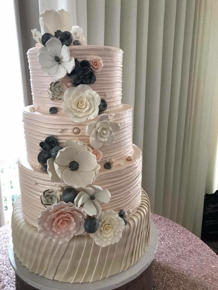 Light pink wedding cake with white and gray sugar flowers
