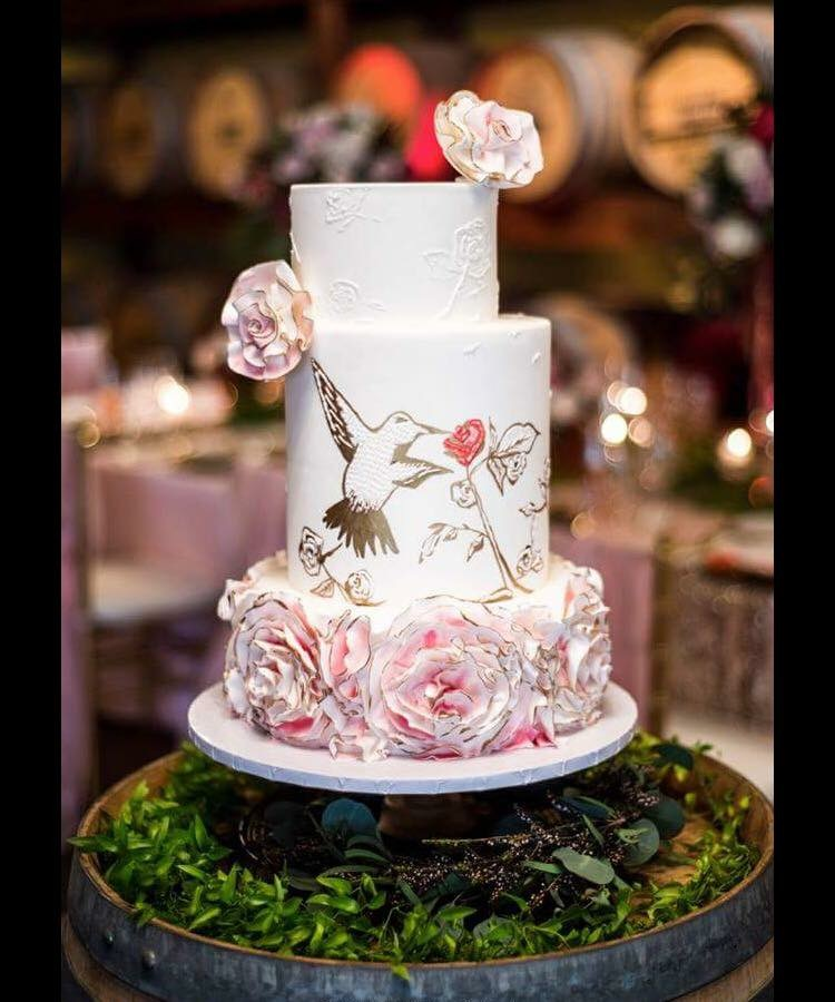 White and pink rosette wedding cake with hand painted gold bird