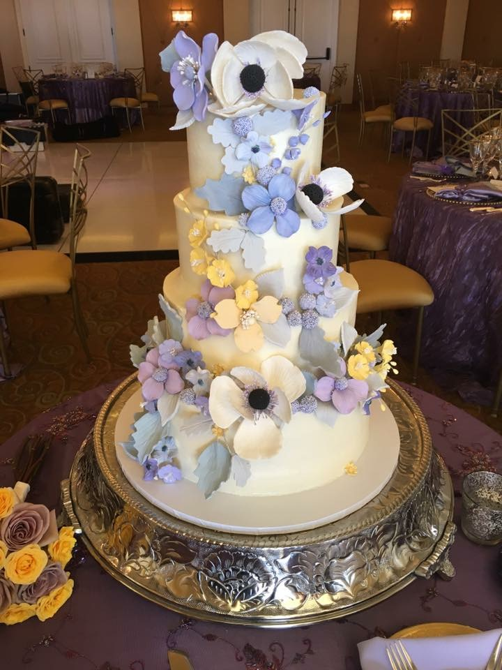 White fondant wedding cake with purple and white sugar flowers