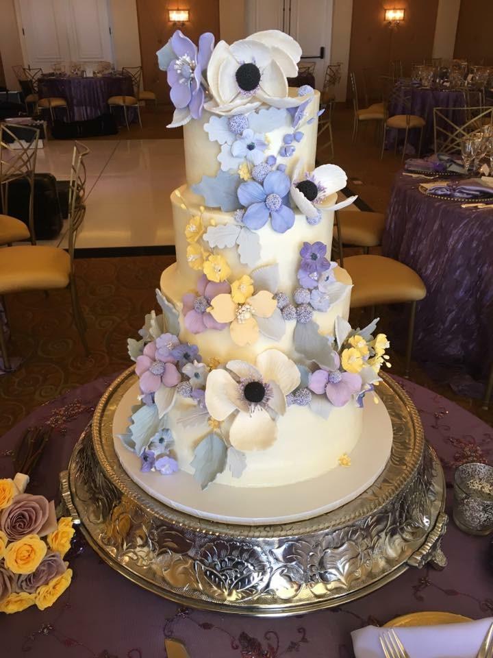 White fondant wedding cake with purple and white sugar flowers