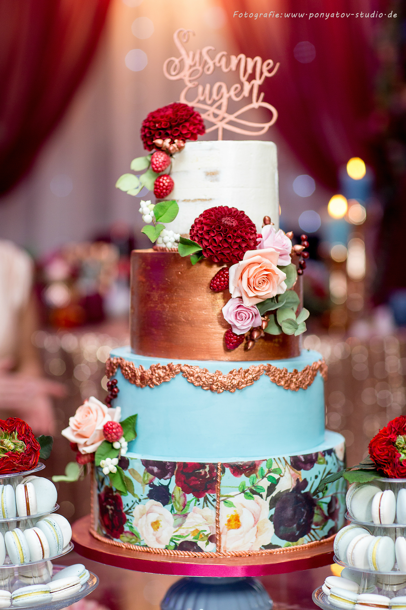 Blue and gold wedding cake with hand painted florals