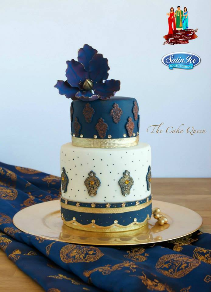 White fondant cake with gold and blue sugar flowers