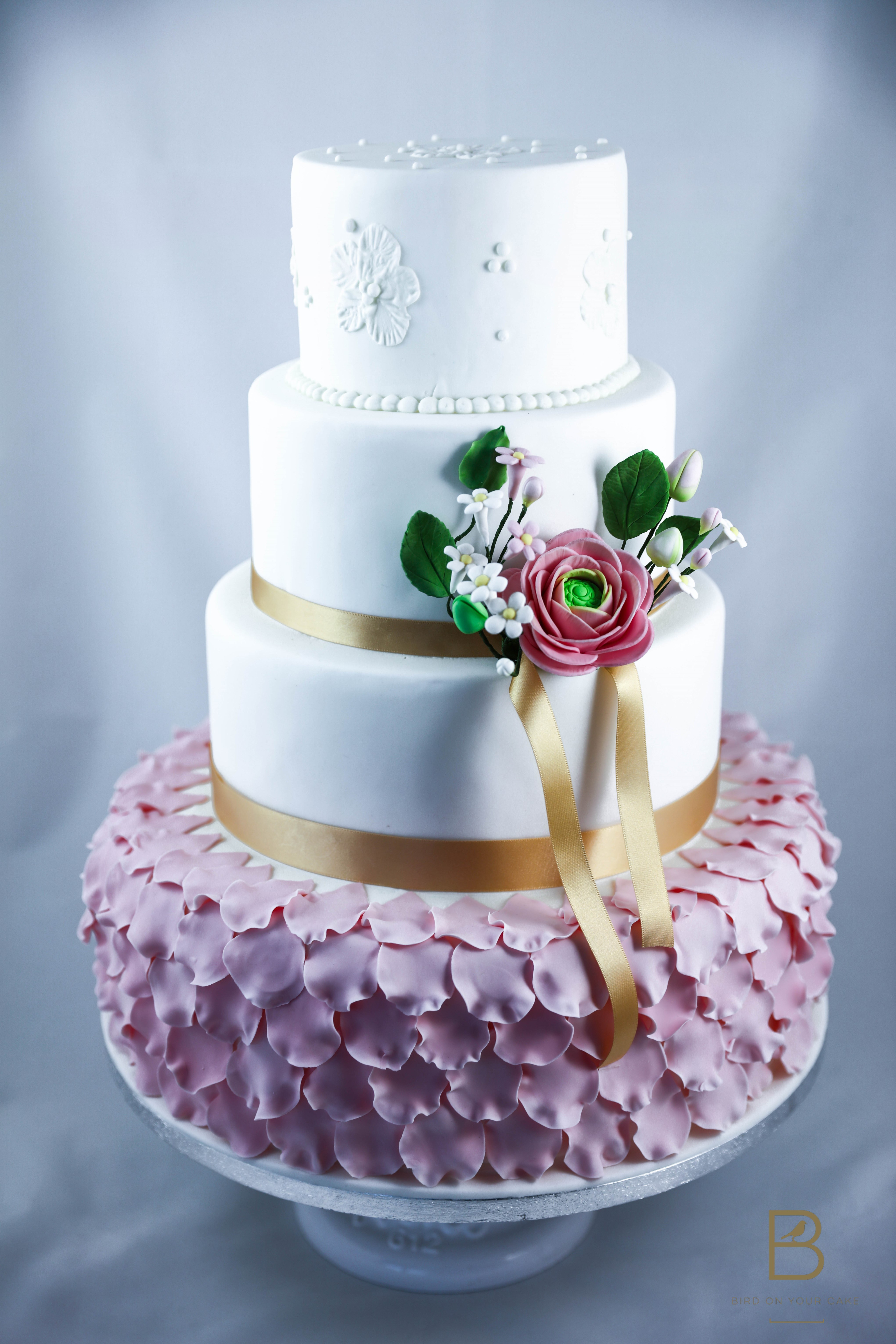White wedding cake with pink ruffles