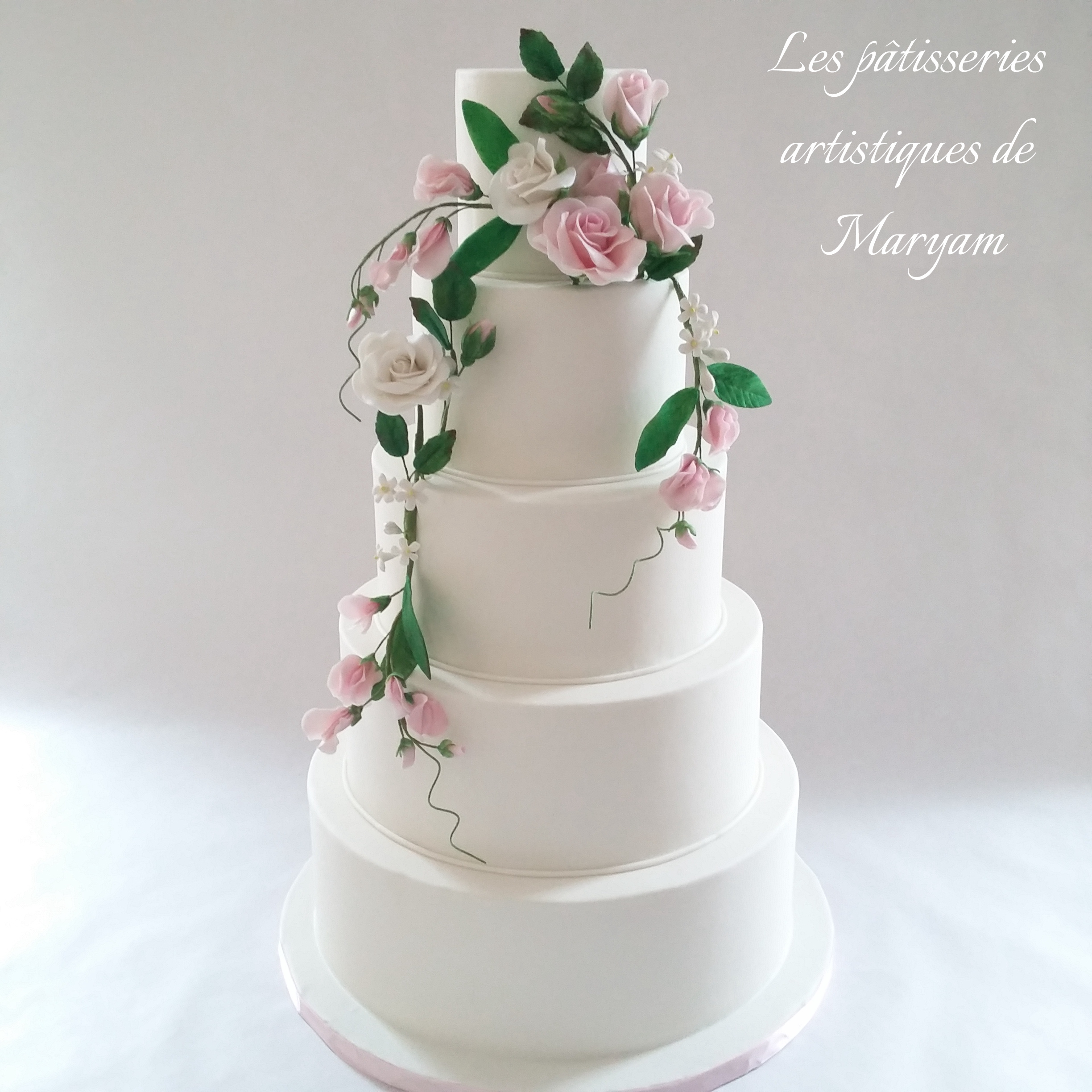 White wedding cake with draping sugar roses