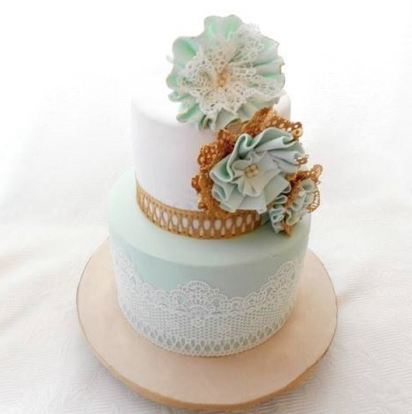 Light blue and white wedding cake with sugar lace and flowers