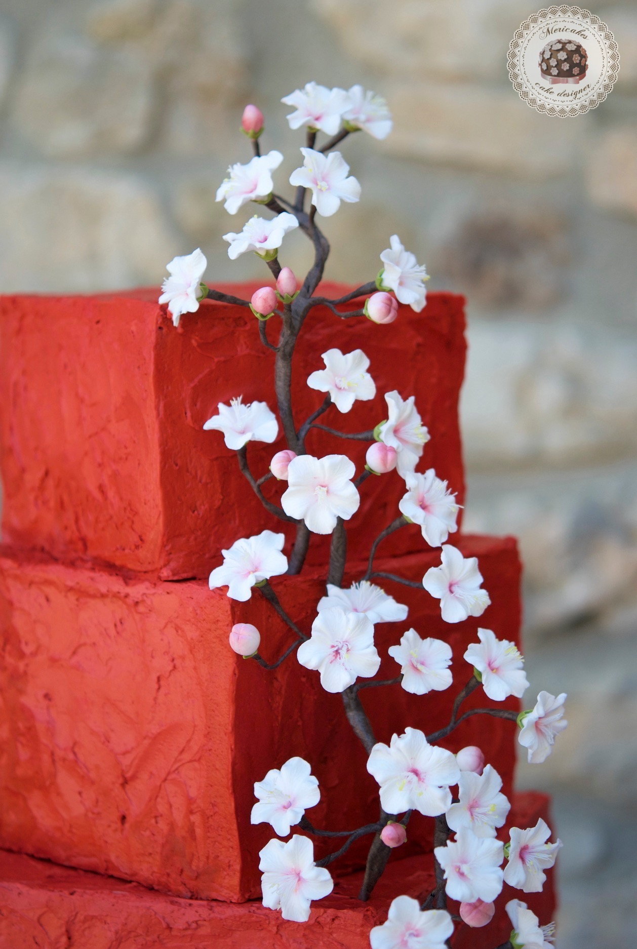 Red wedding cake with cherry blossom sugar flowers