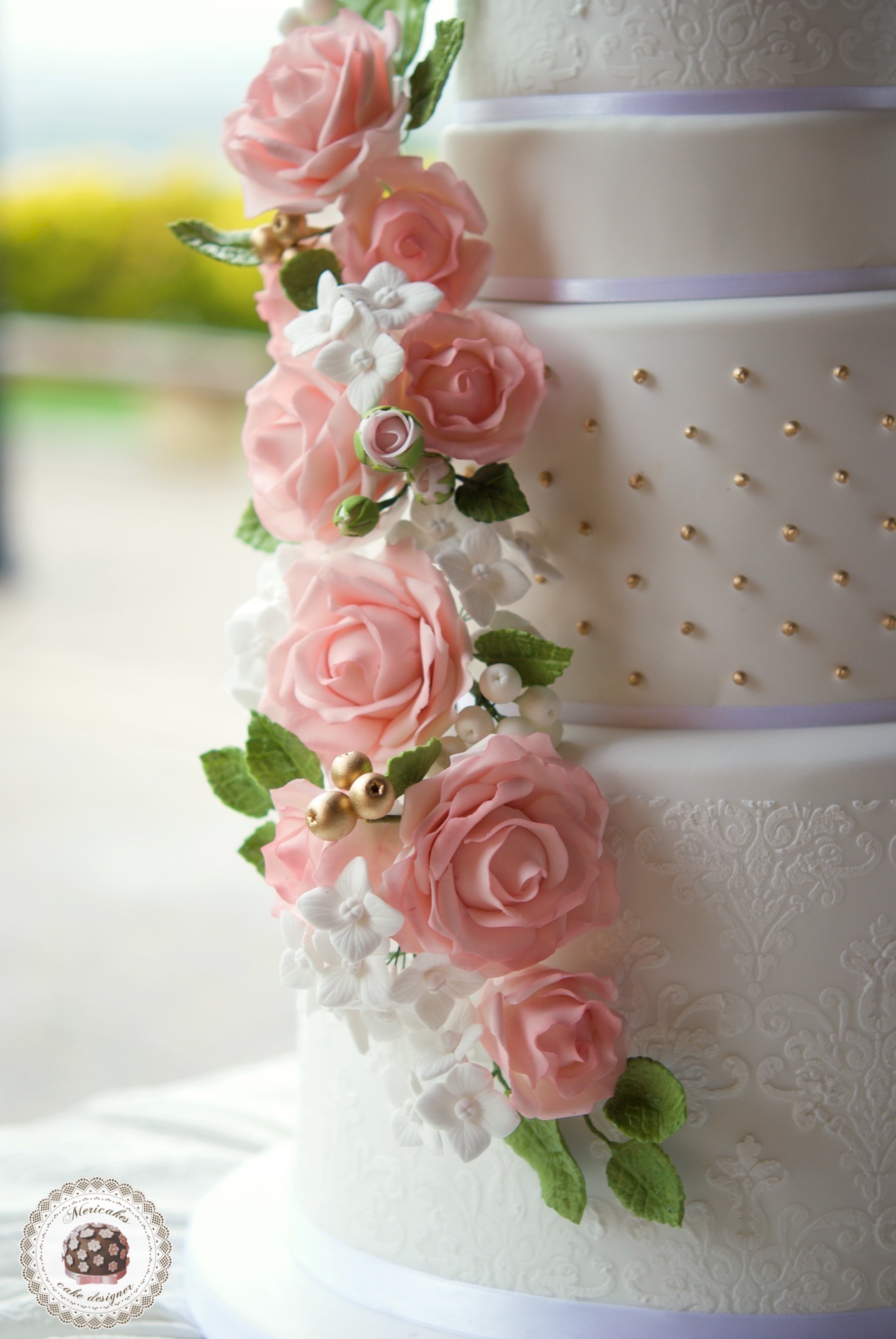 White wedding cake with gold pearls and pink sugar flowers