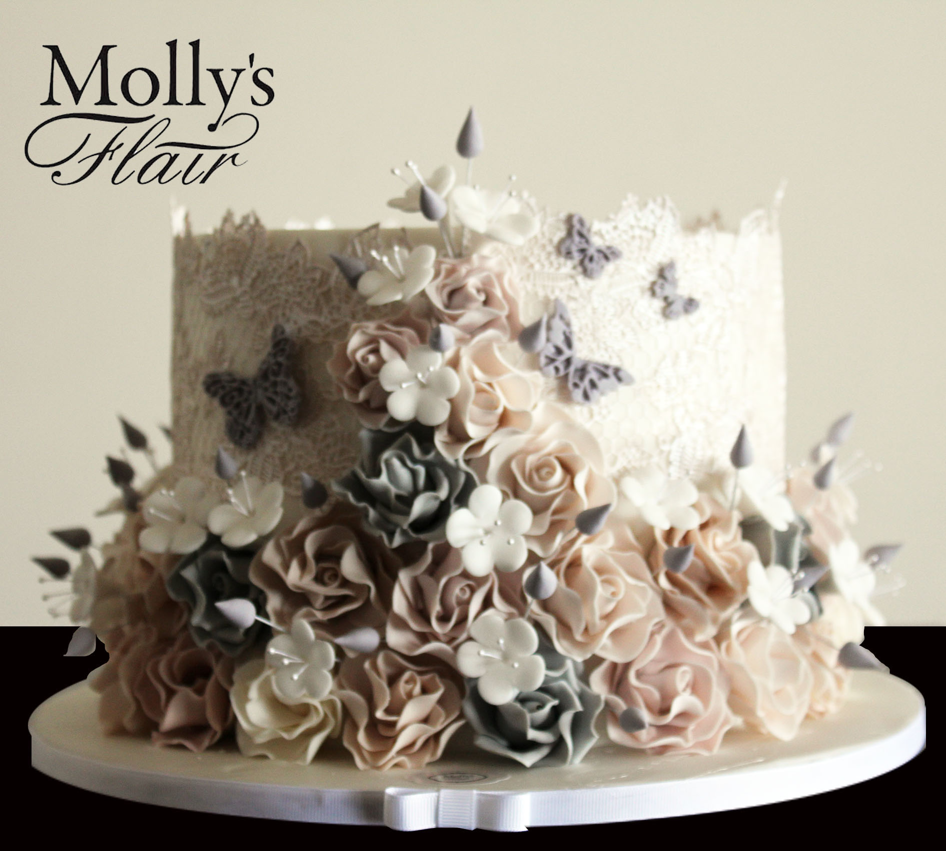 White cake with cascading sugar flowers and butterflies