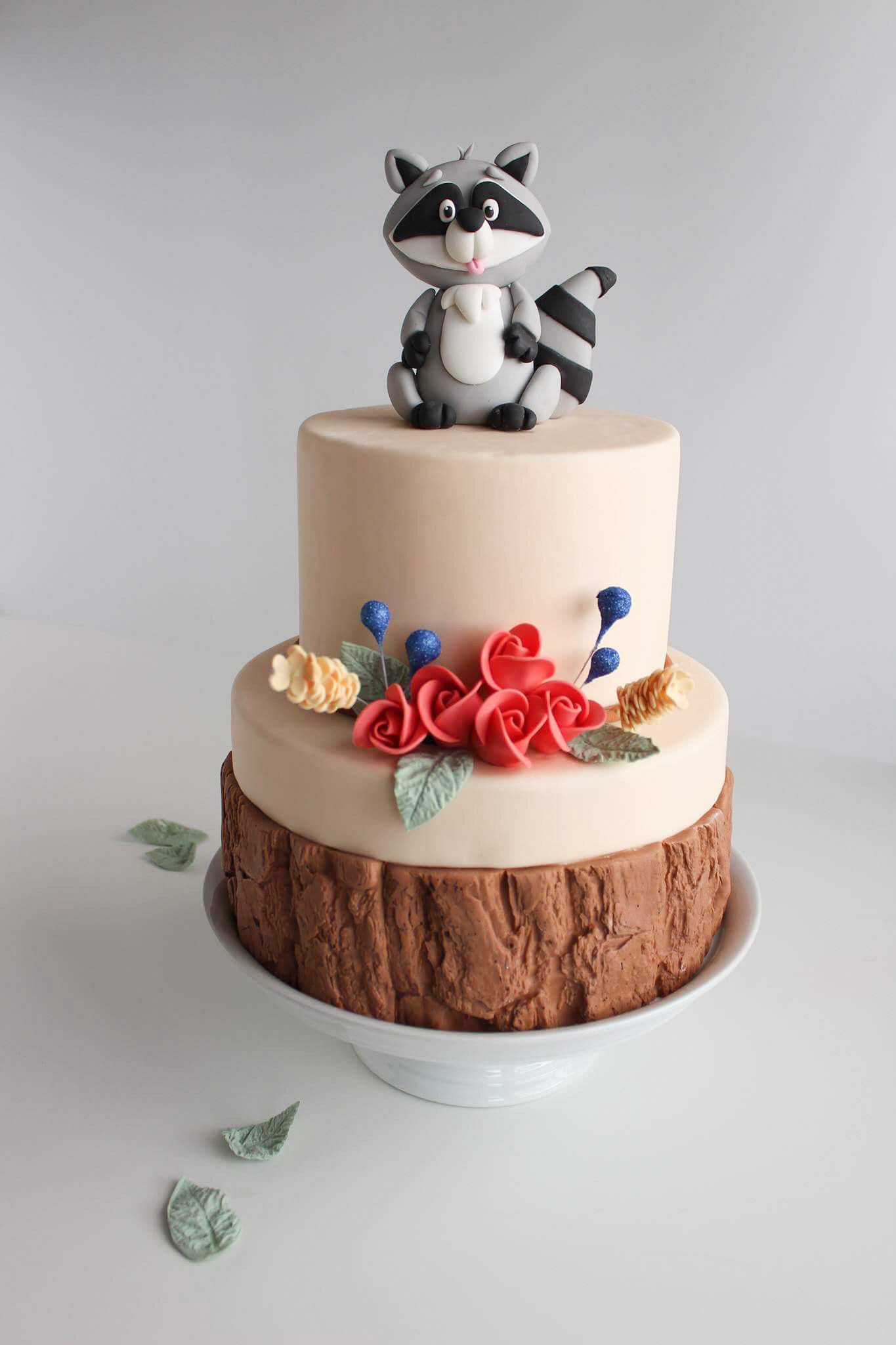 Baby pink rustic wood birthday cake with raccoon topper