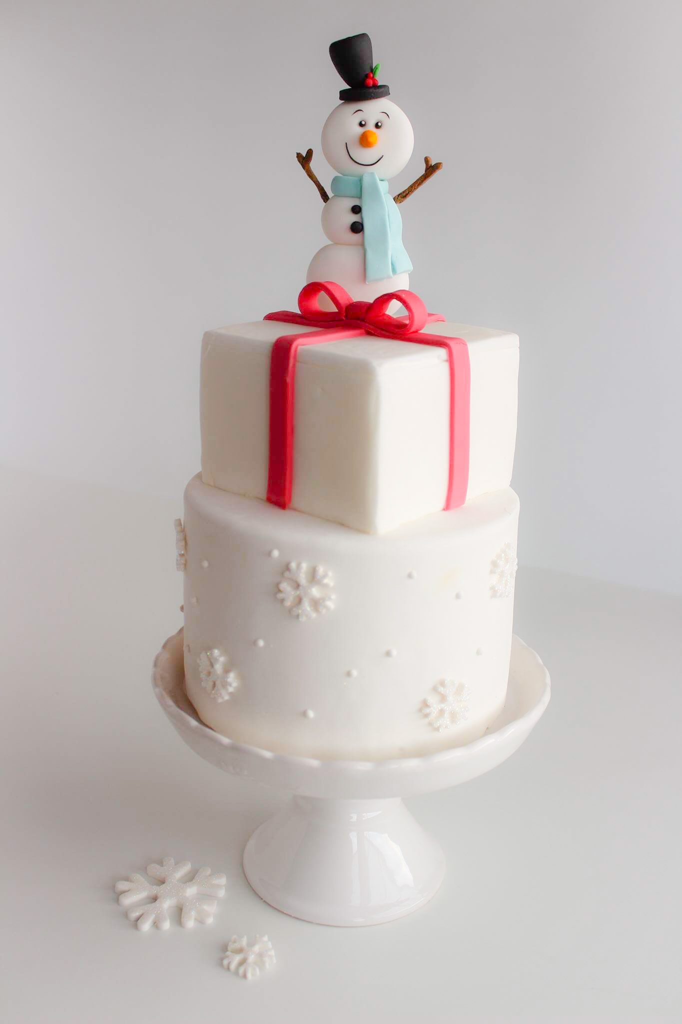 White fondant cake with snowman topper