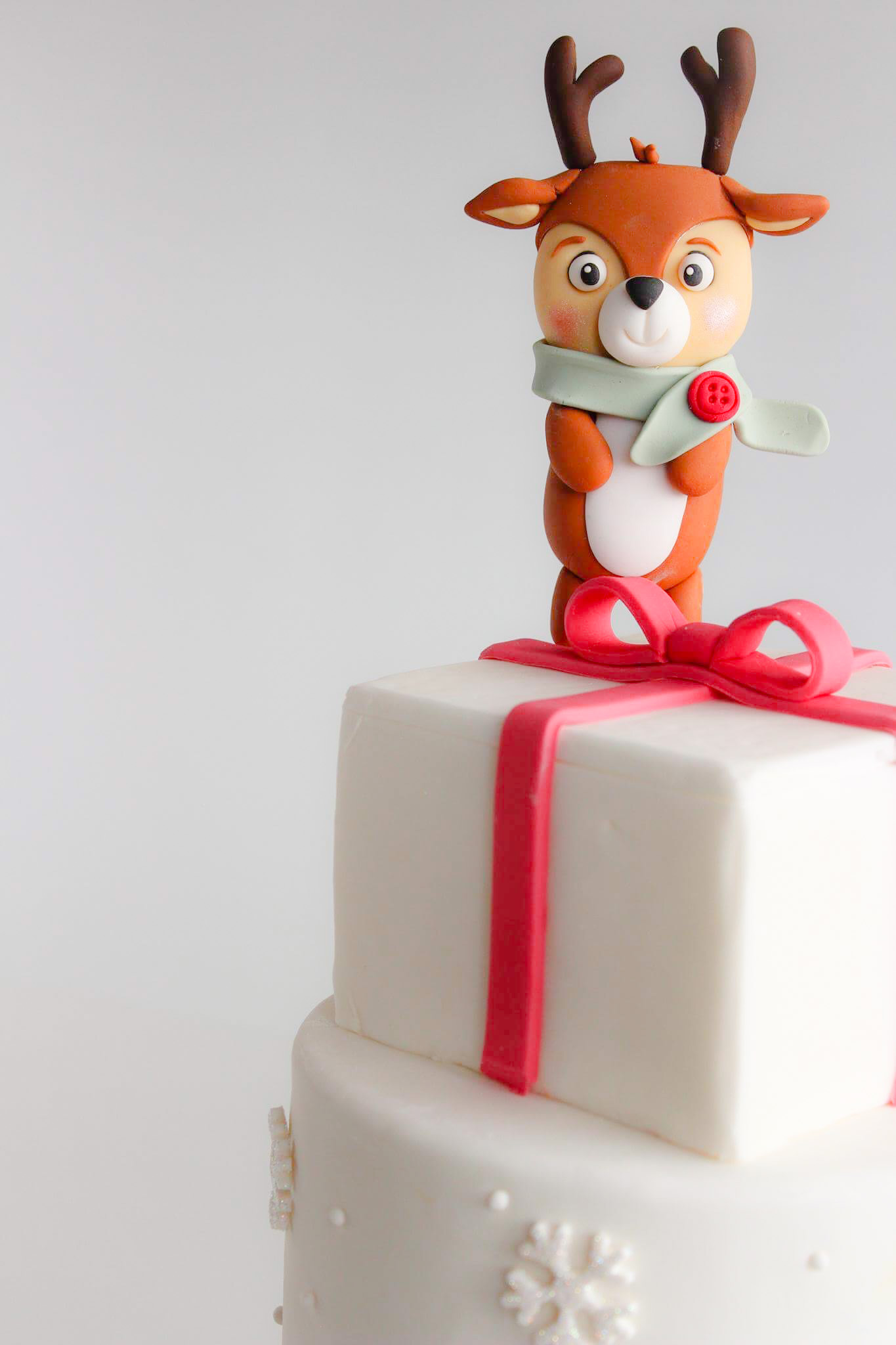 White fondant cake with reindeer topper
