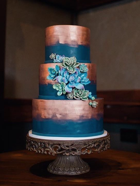 Blue and copper fondant wedding cake with blue sugar flowers