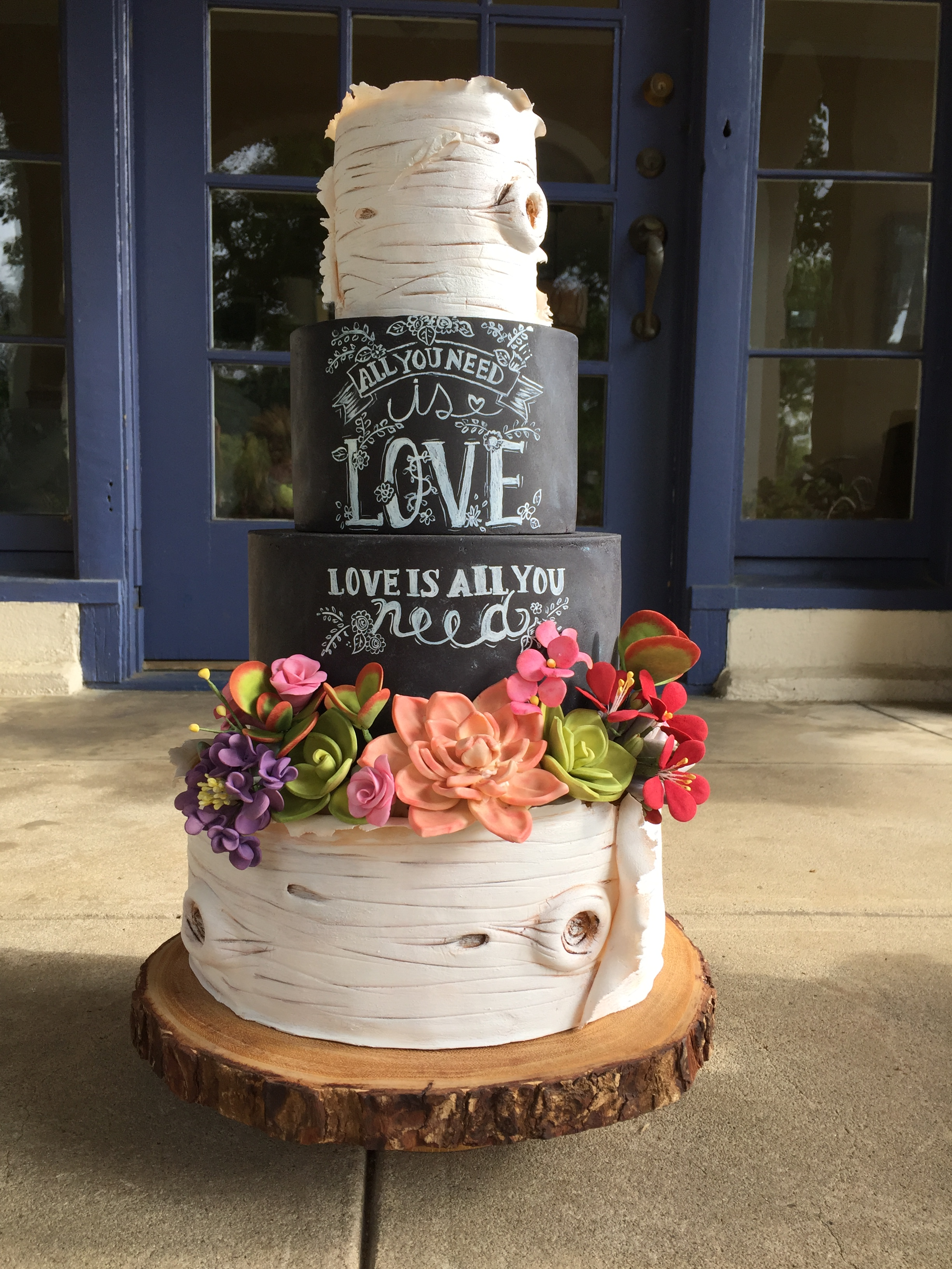 Chalkboard and bark wedding cake with sugar succulents