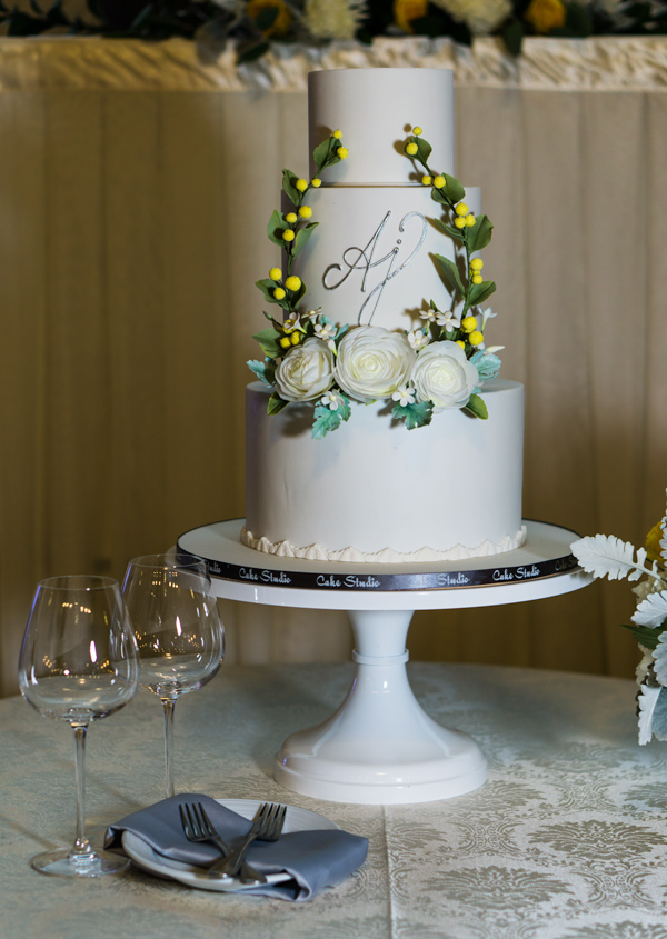 White monogramed fondant wedding cake with gum paste greenery