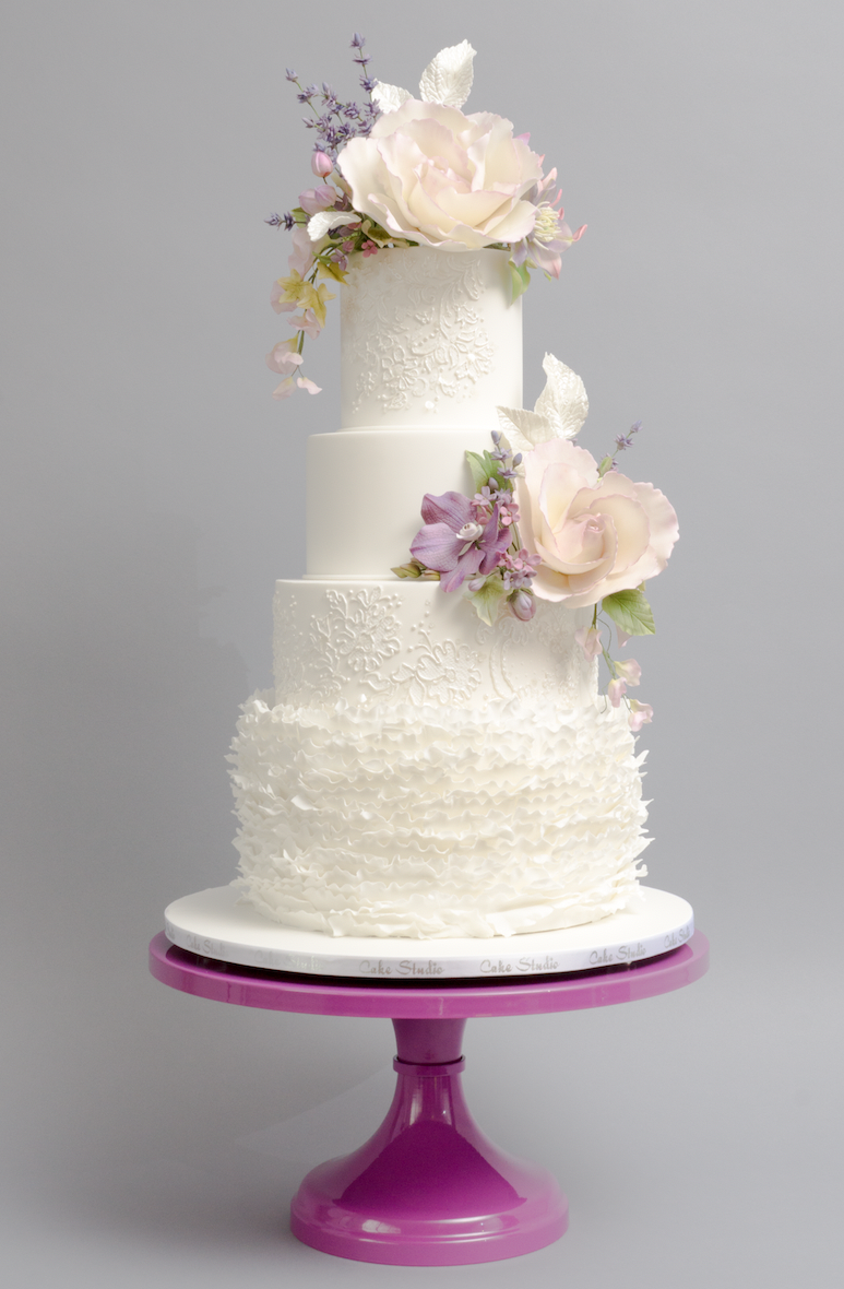 All white ruffle frill wedding cake with pastel pink sugar flowers