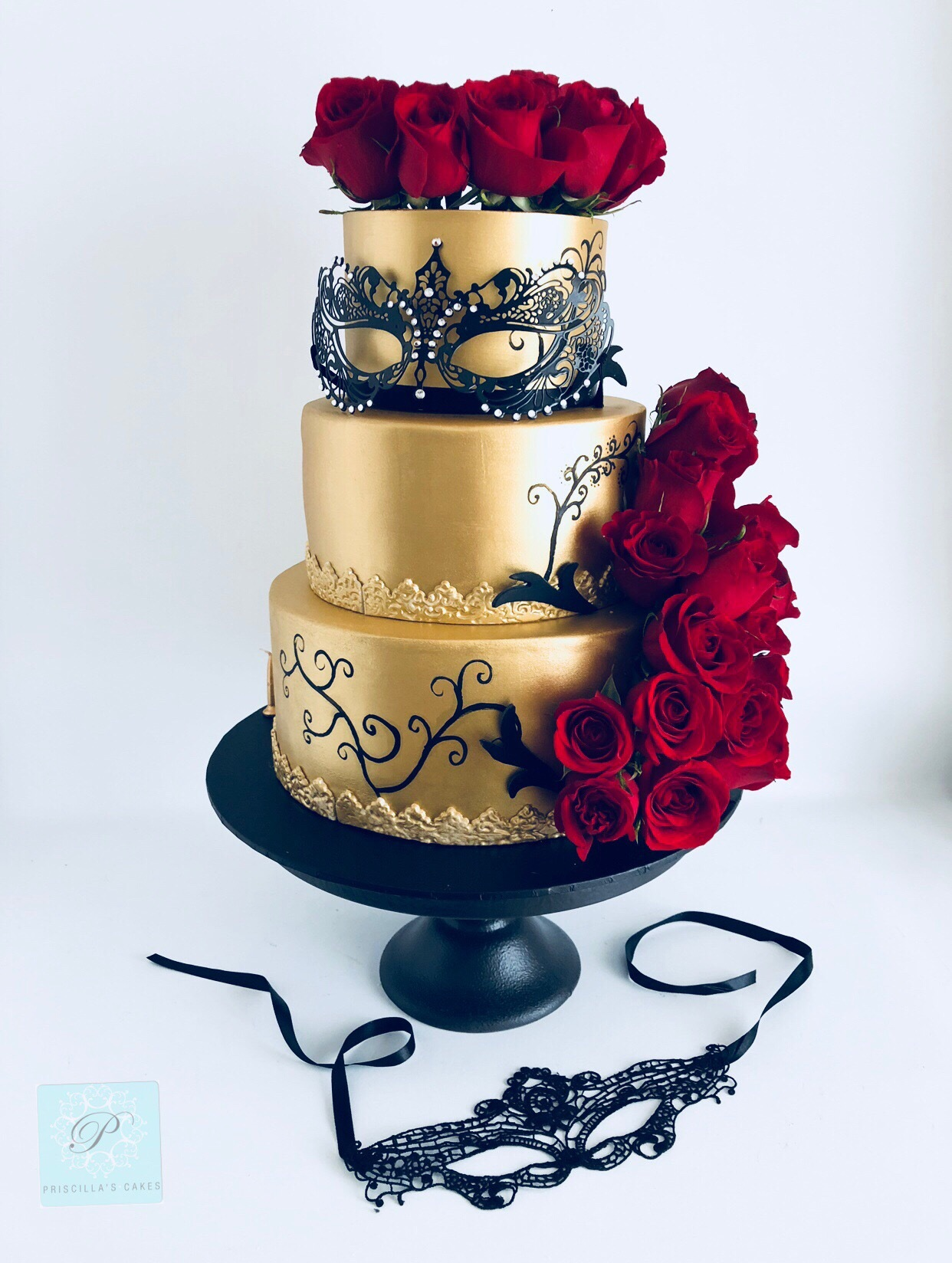 Gold wedding cake with red sugar flowers