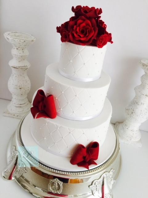 White fondant wedding cake with red sugar flowers