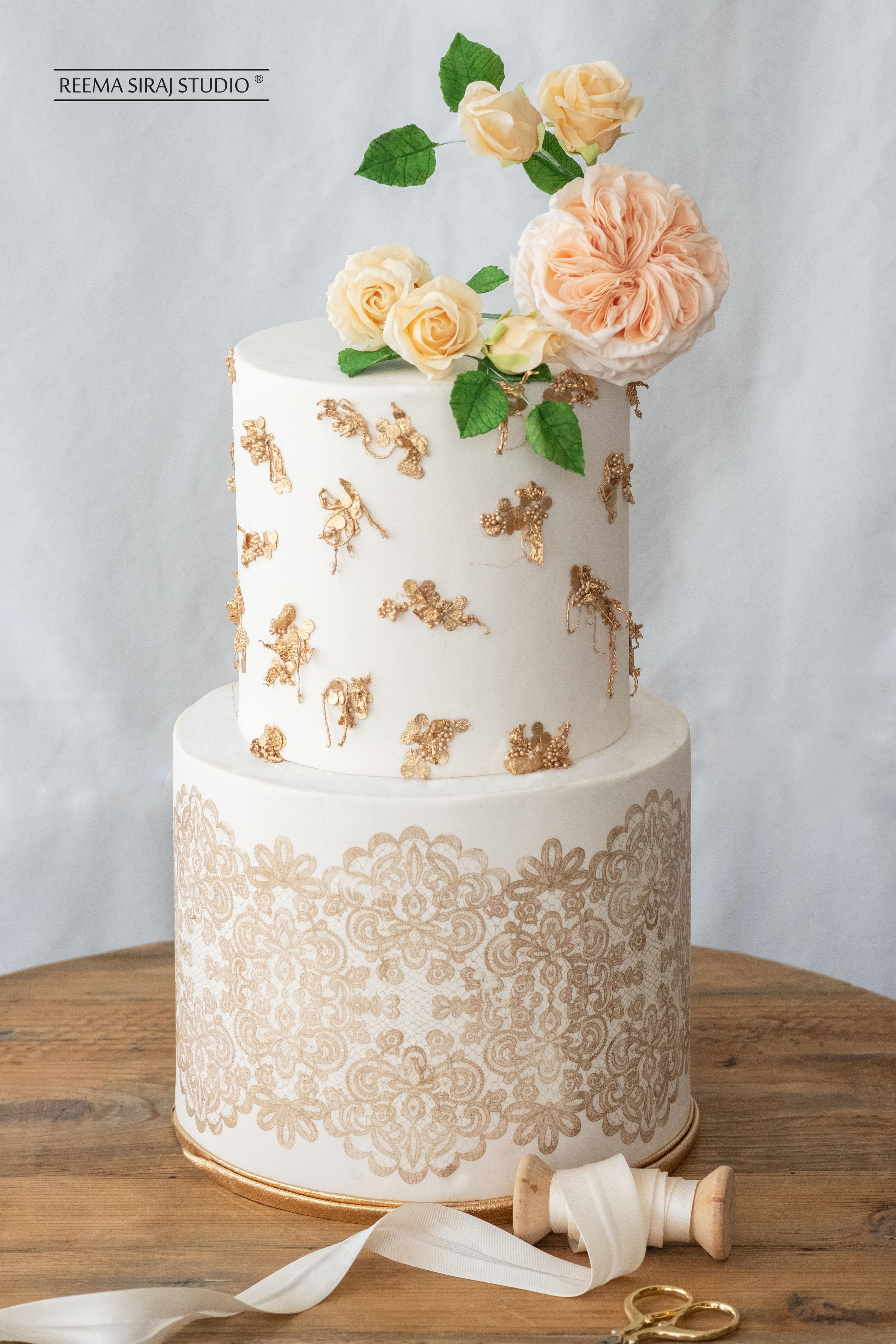 White fondant wedding cake with gold detailing