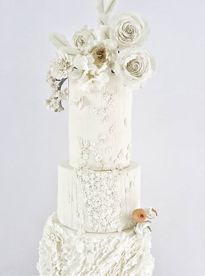 All white fondant wedding cake with rosette ruffles