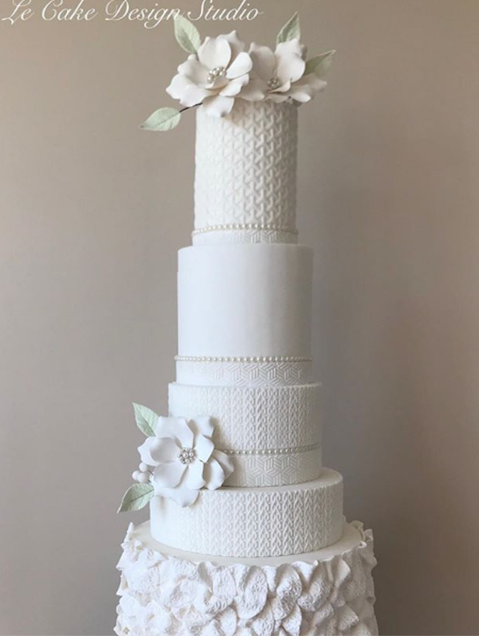 All white fondant wedding cake with ruffles