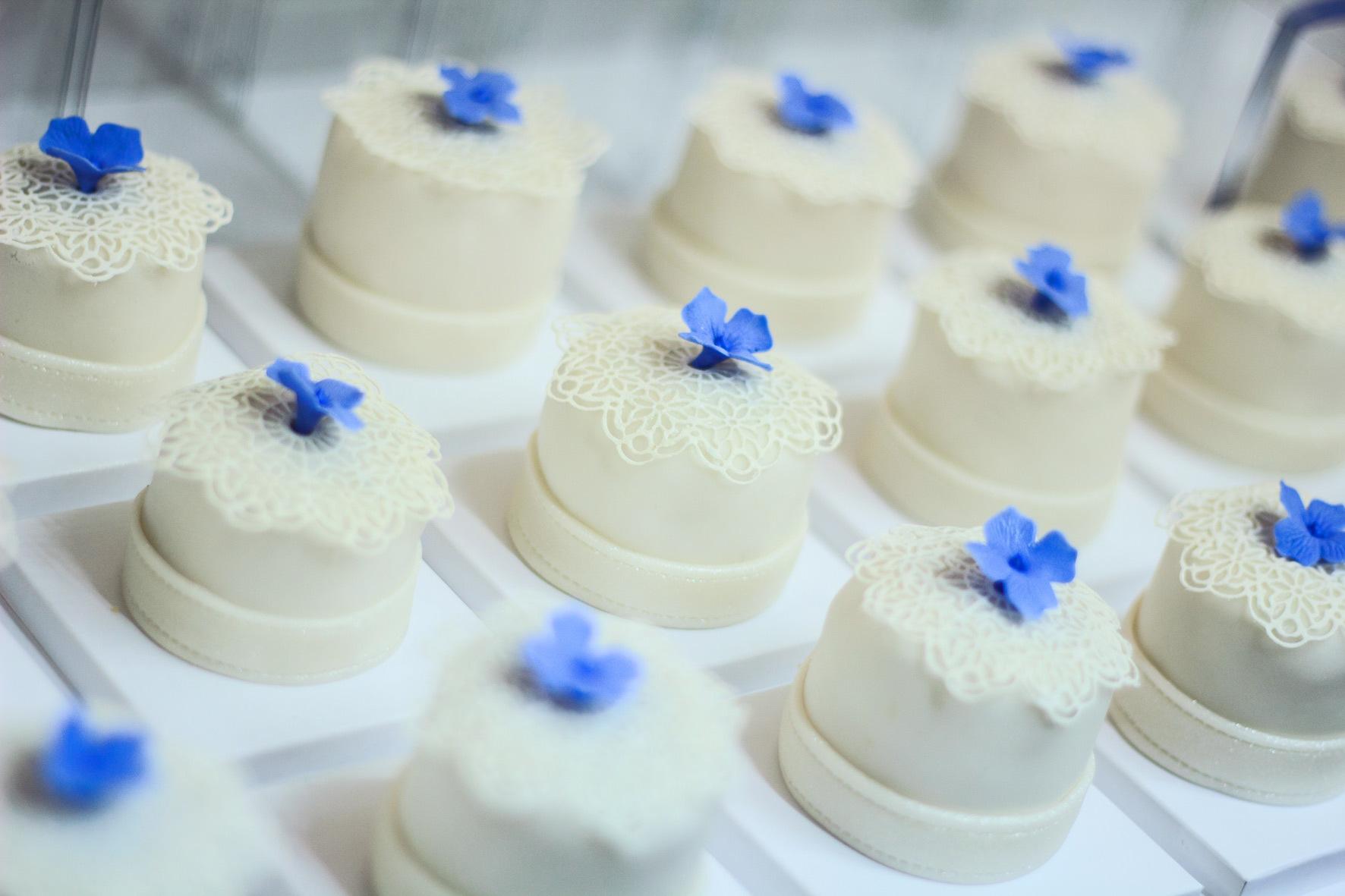 Tiny ivory fondant wedding cakes with blue flowers