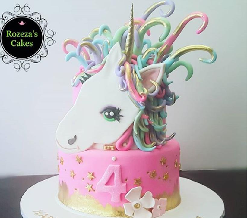 Bright pink and white fondant unicorn birthday cake