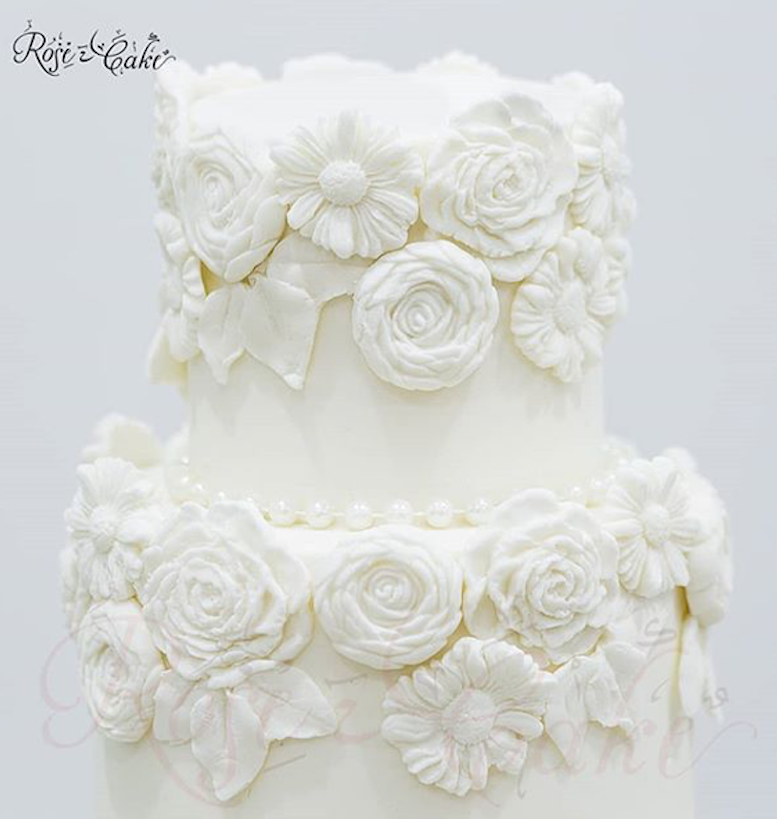 All white fondant wedding cake with bas relief flowers