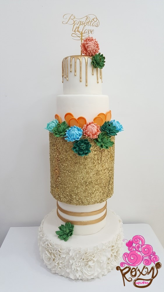 White drip wedding cake with ruffles and gold sequins