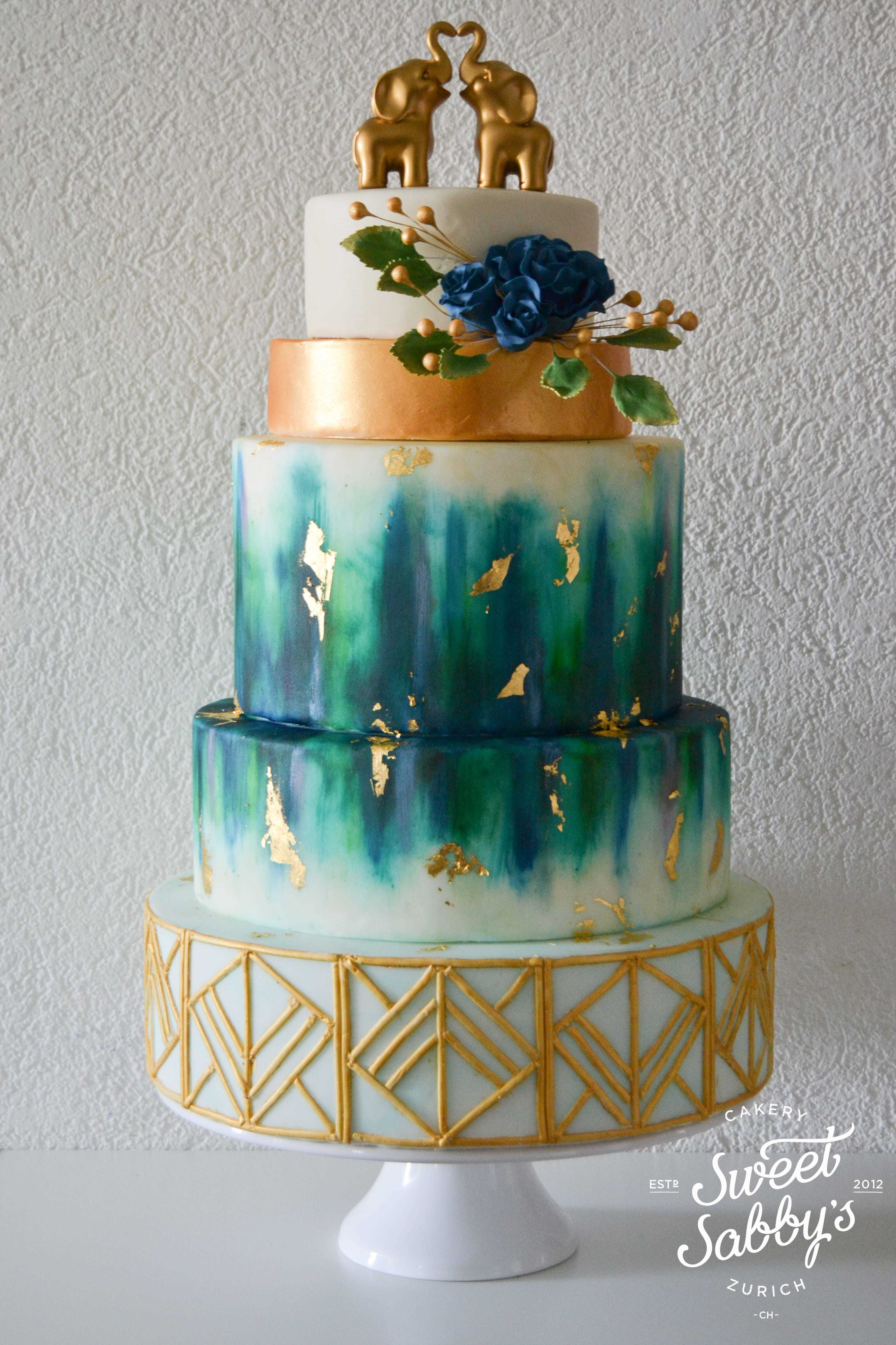Gold trimmed peacock fondant wedding cake