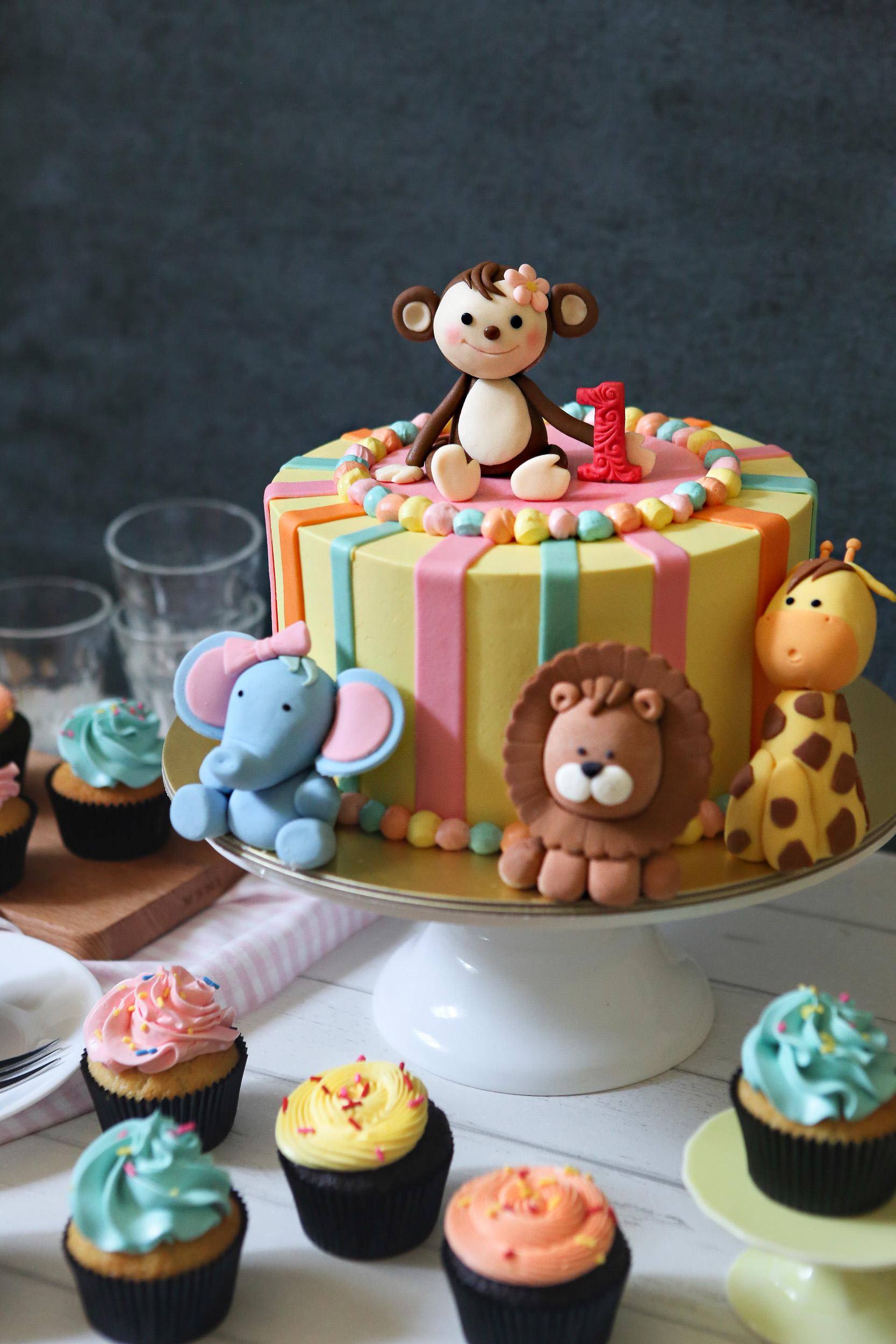 Candy striped birthday cake with safari animal toppers