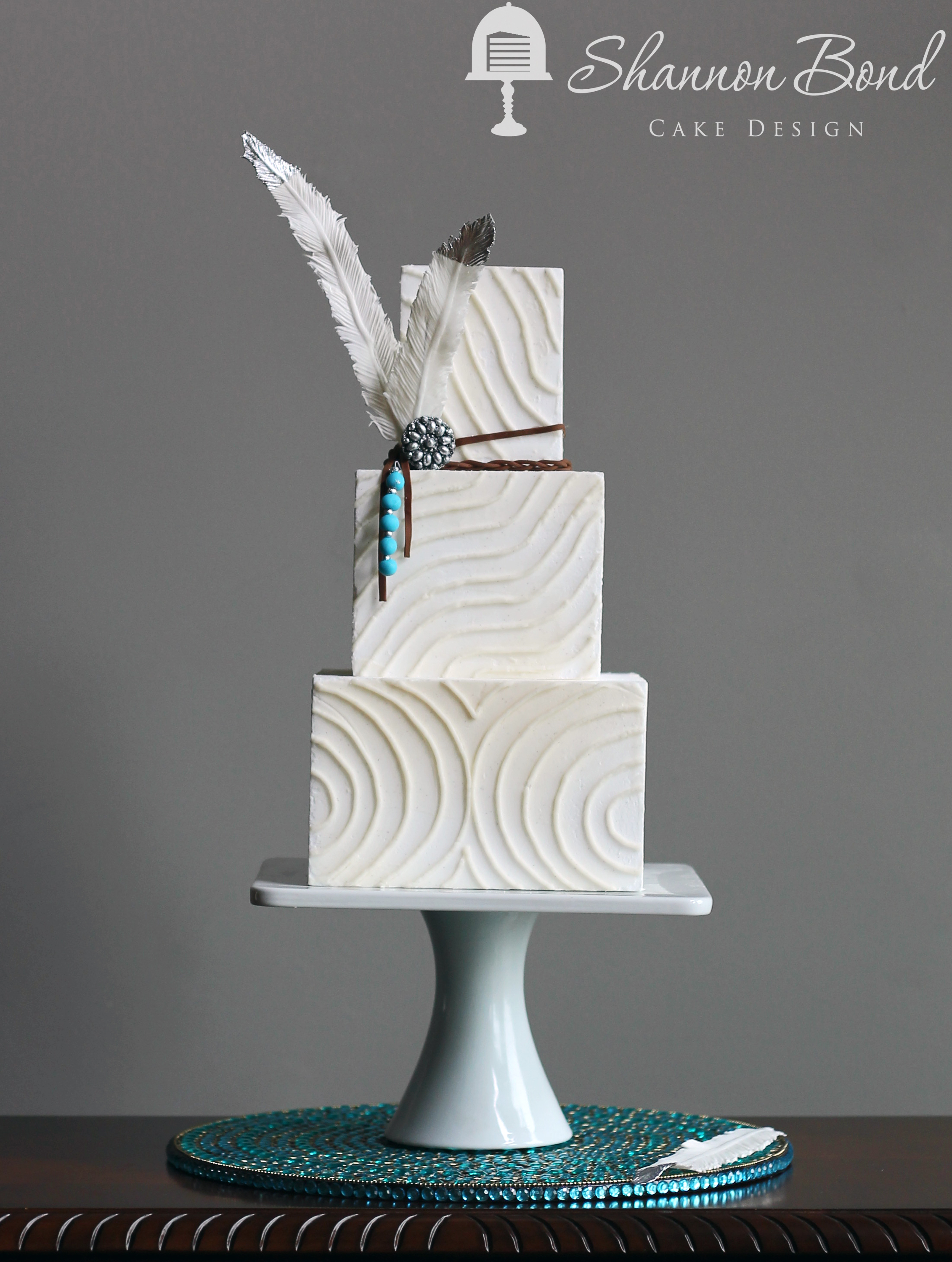 White Bohemian fondant wedding cake with feather
