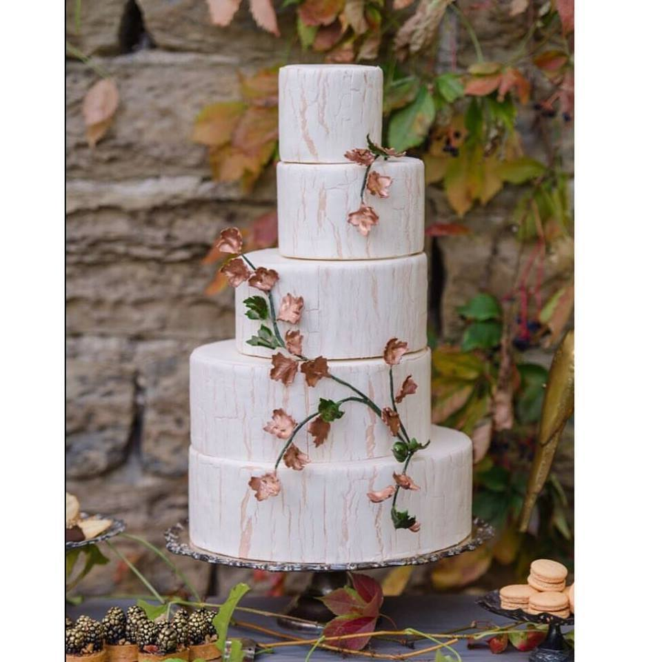 White fondant wedding cake with fall foliage details