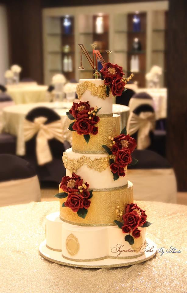 Gold and white wedding cake with burgundy sugar flowers