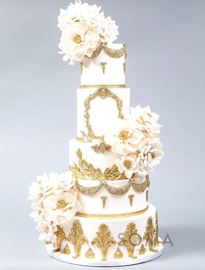 White fondant wedding cake with gold detailing