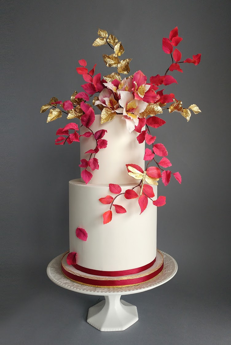 White wedding cake with red and gold sugar leaves