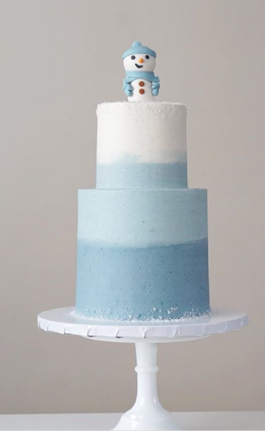 Blue and white cake with fondant snowman topper