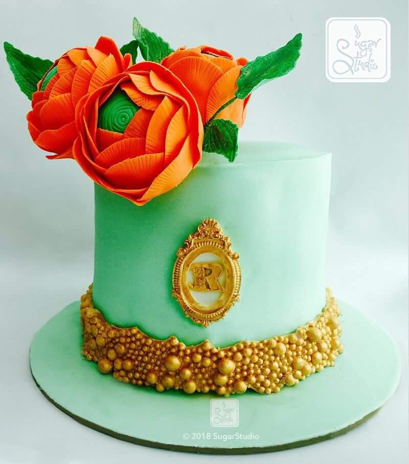 pastel green cake with orange sugar flowers