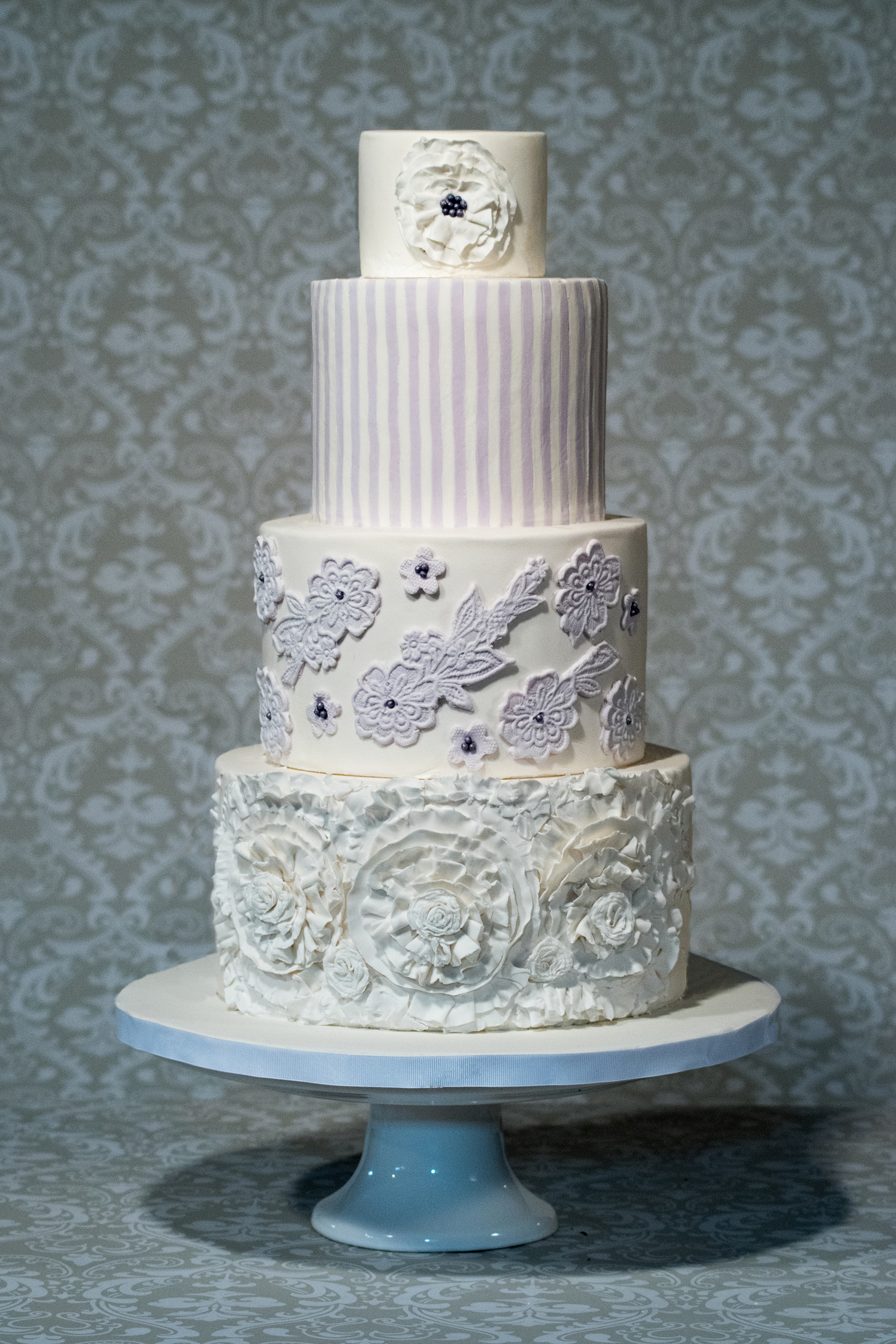 White striped wedding cake with rosettes