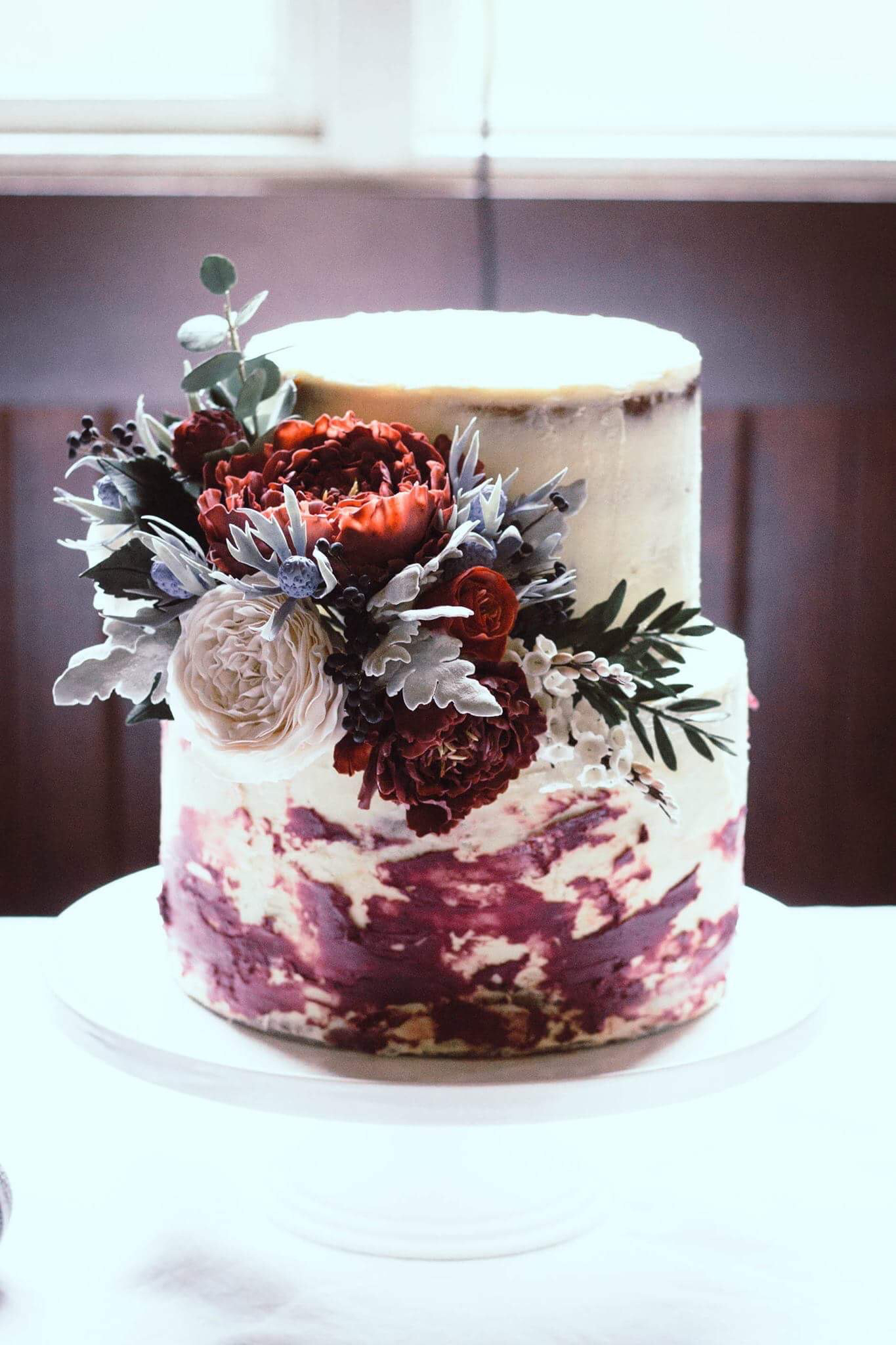 Naked wedding cake with burgundy sugar flowers