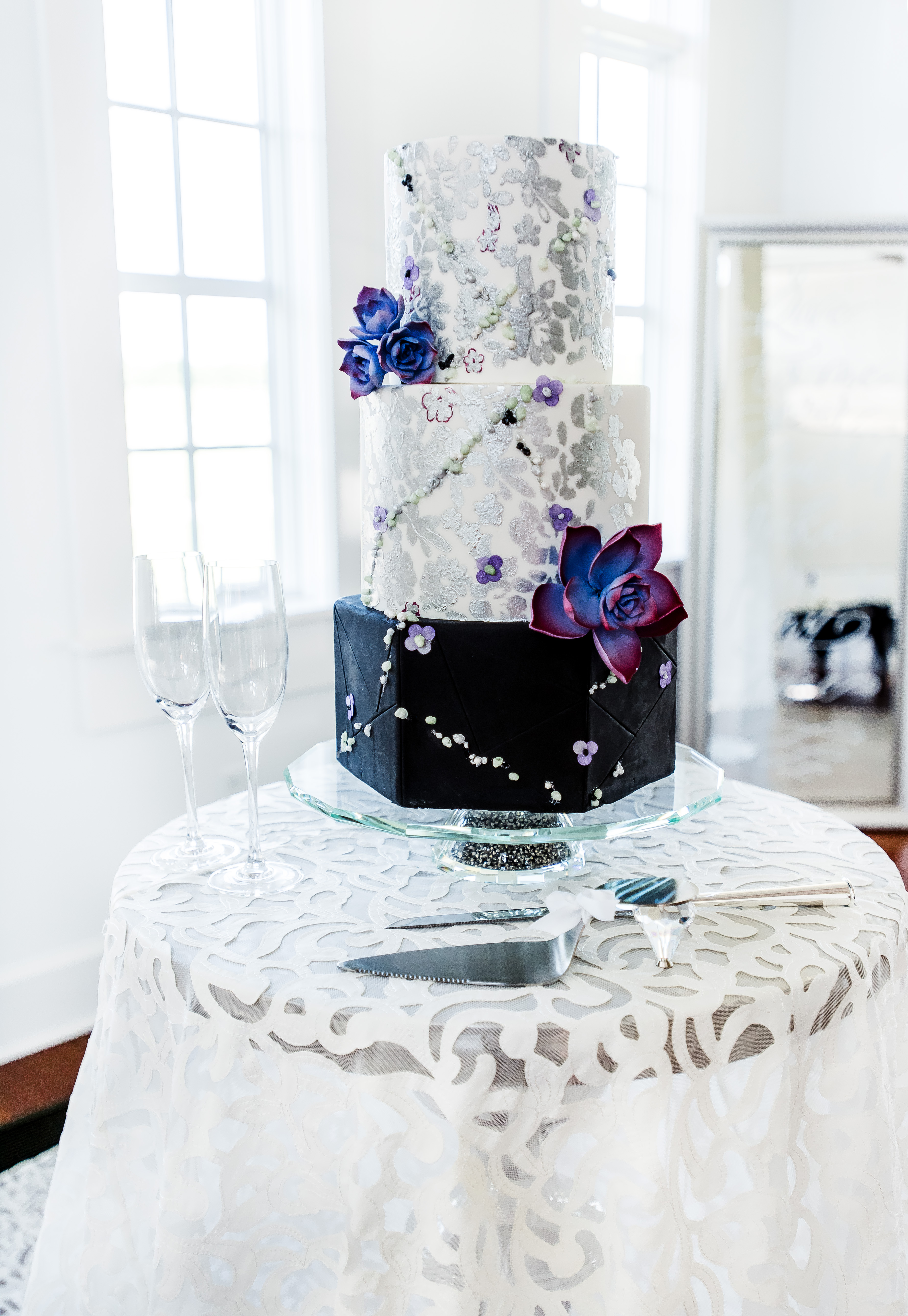 Black and white wedding cake with silver hand painted flowers