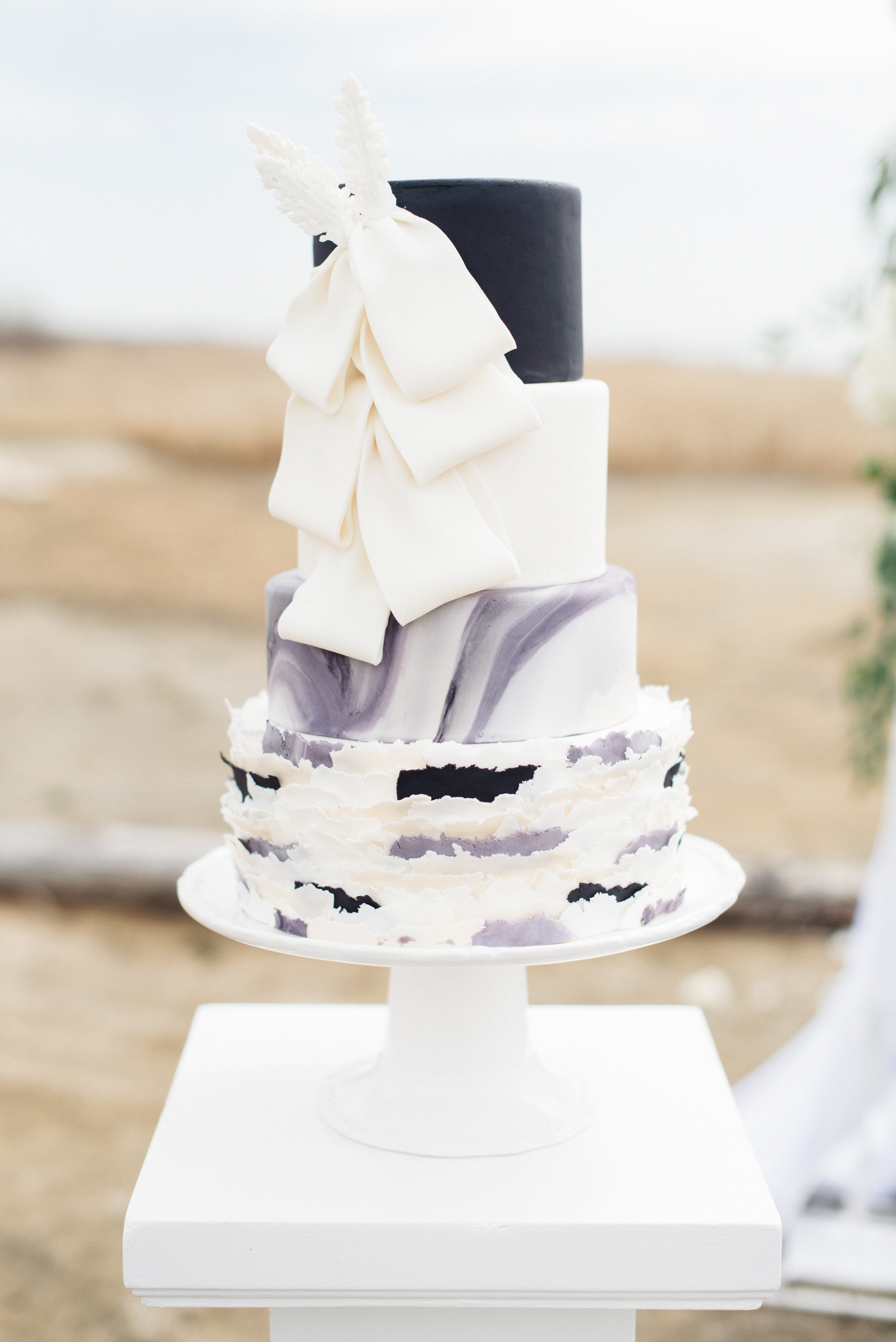 Black and white marbled wedding cake with sugar bow