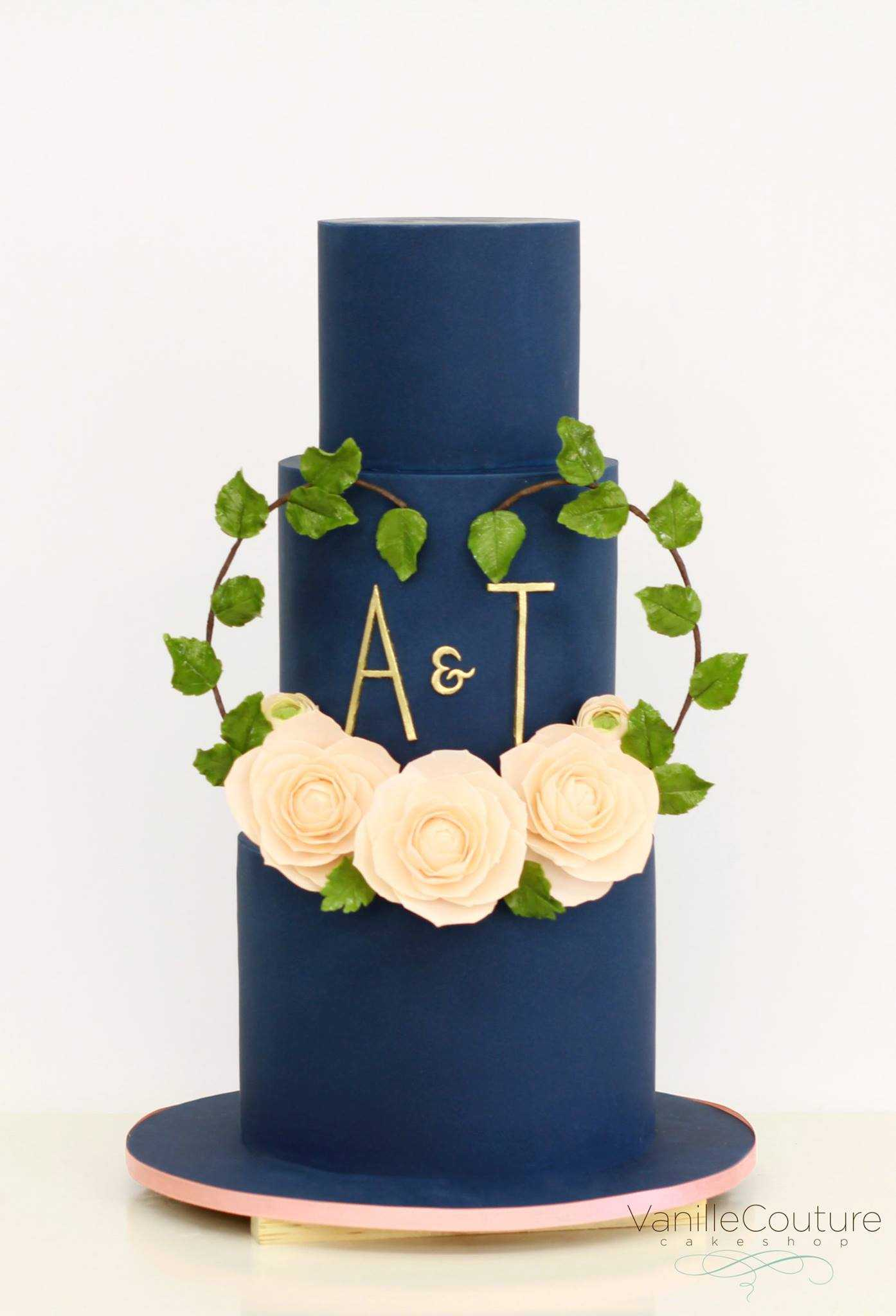 Navy blue fondant wedding cake with peach sugar flowers