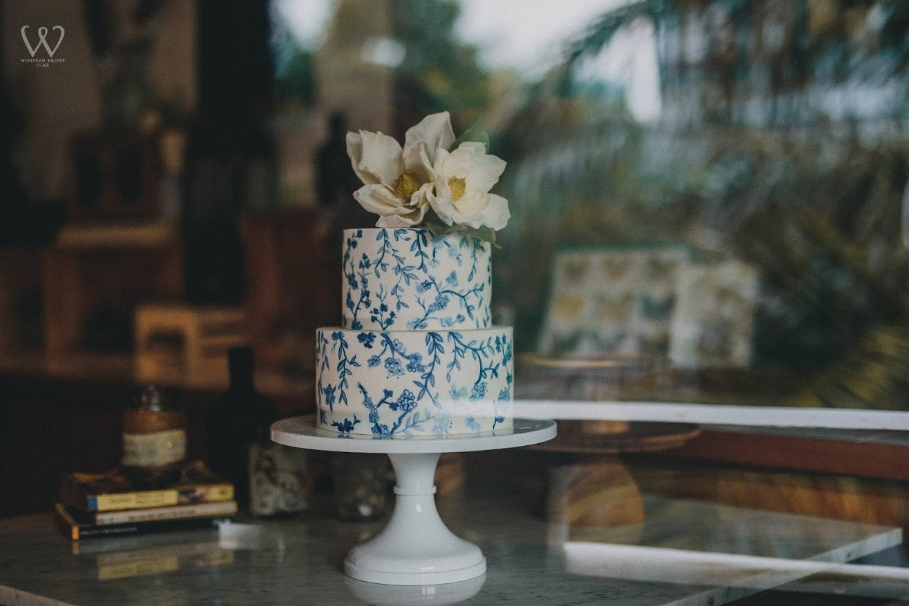 White fondant wedding cake with hand painted blue flowers