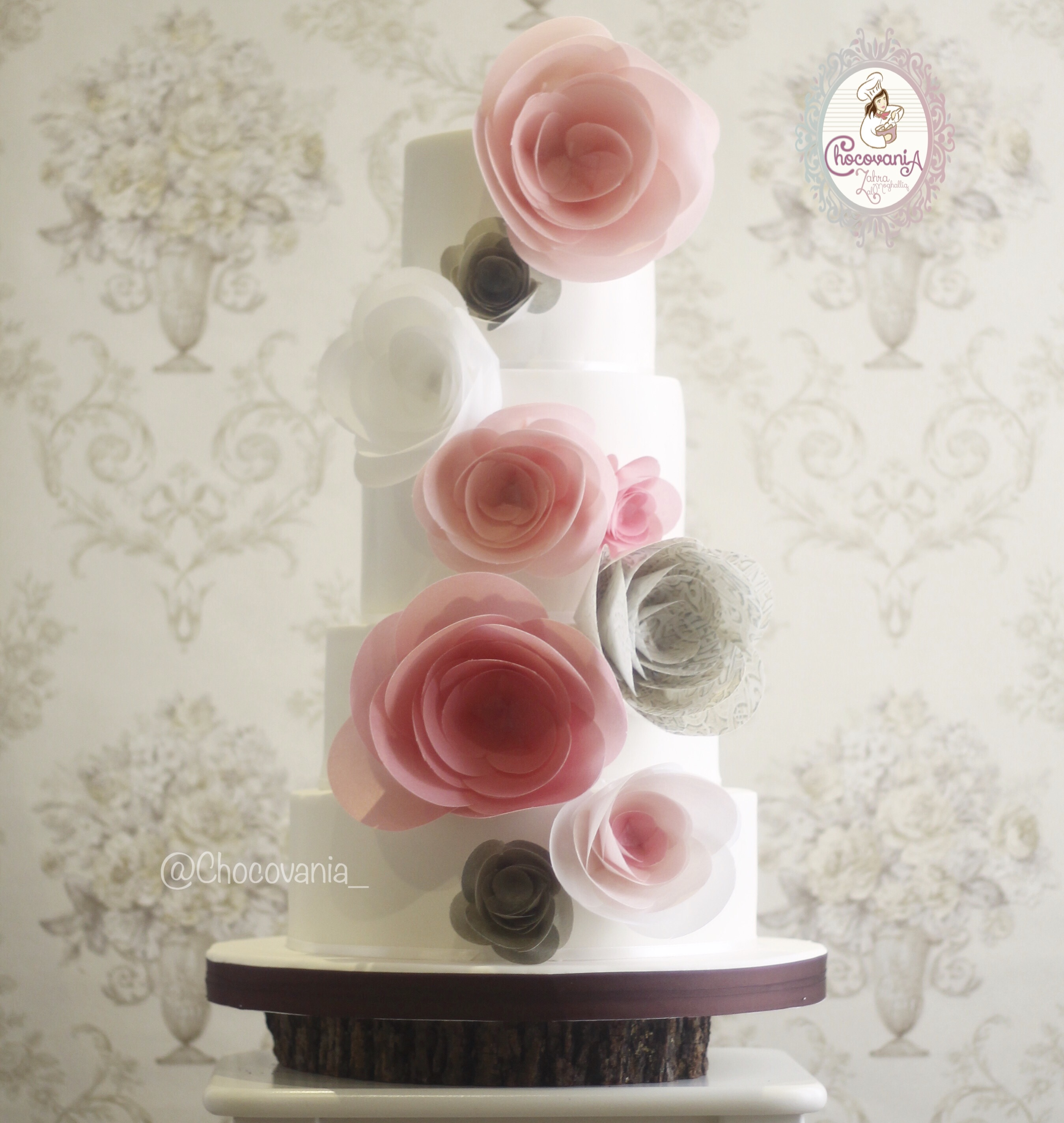 White wedding cake with pink and gray wafer flowers