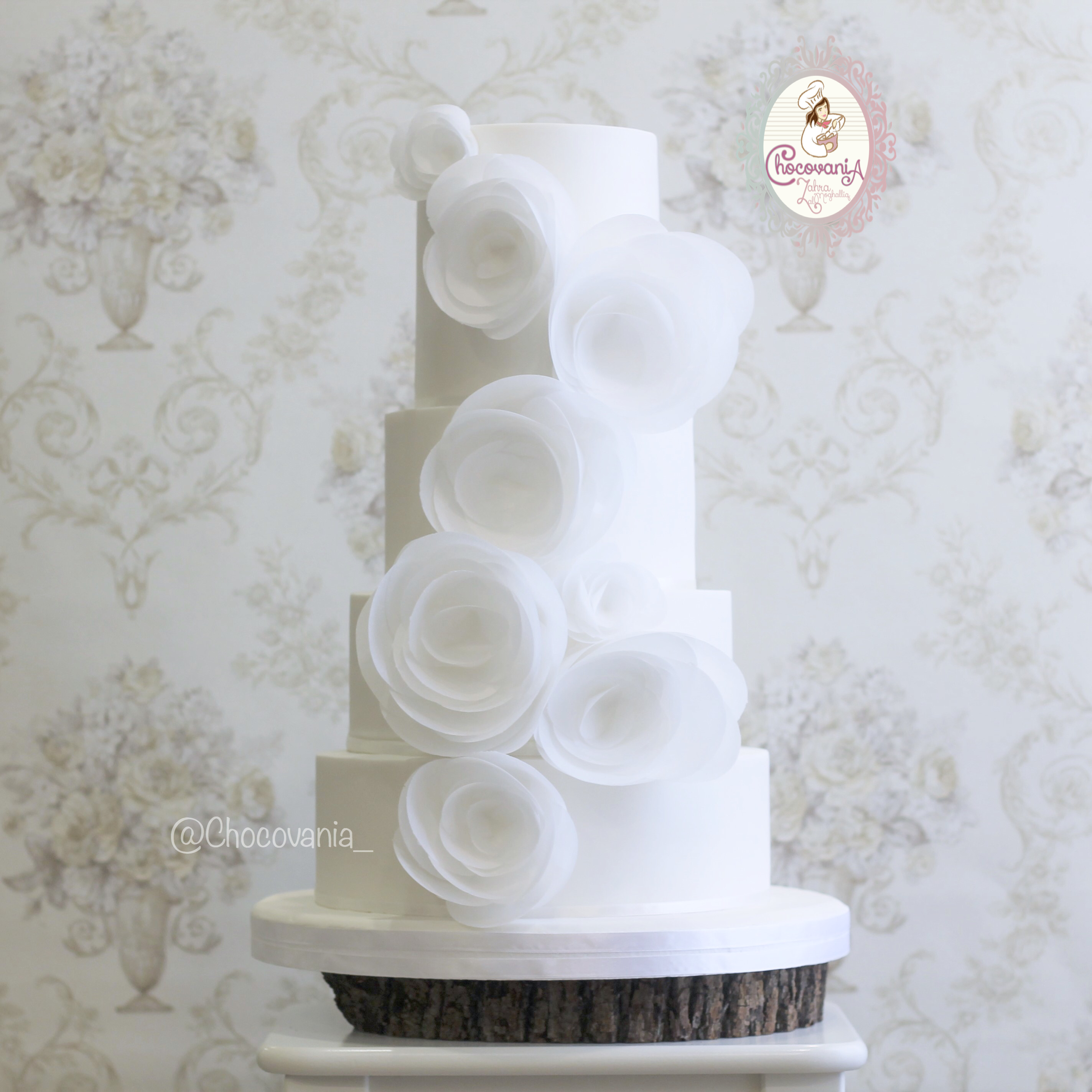 White wedding cake with large wafer flowers