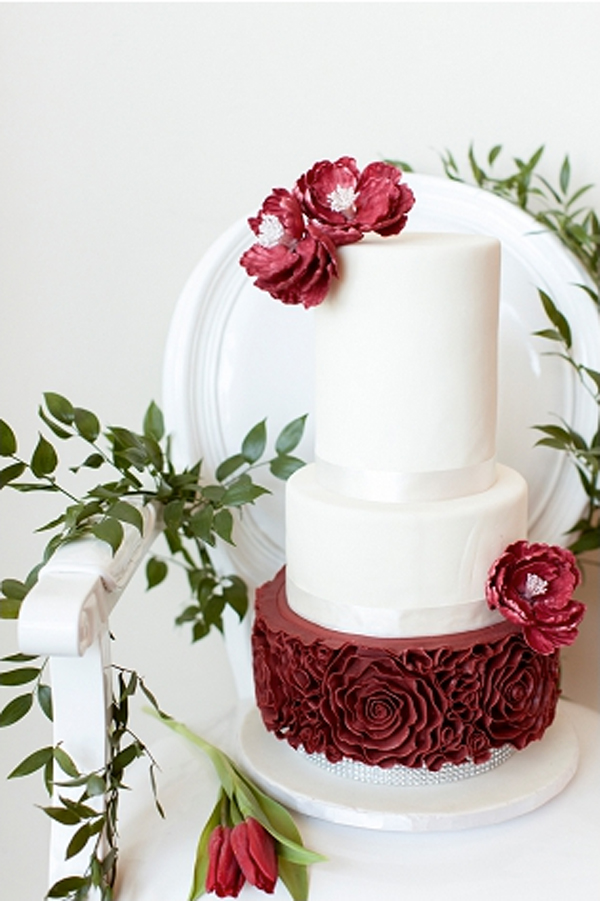 White fondant wedding cake with red rosette tier