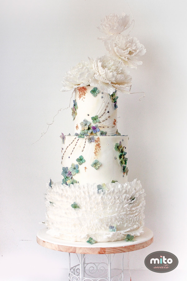 White fondant wedding cake with ruffling and white sugar flowers and green accents